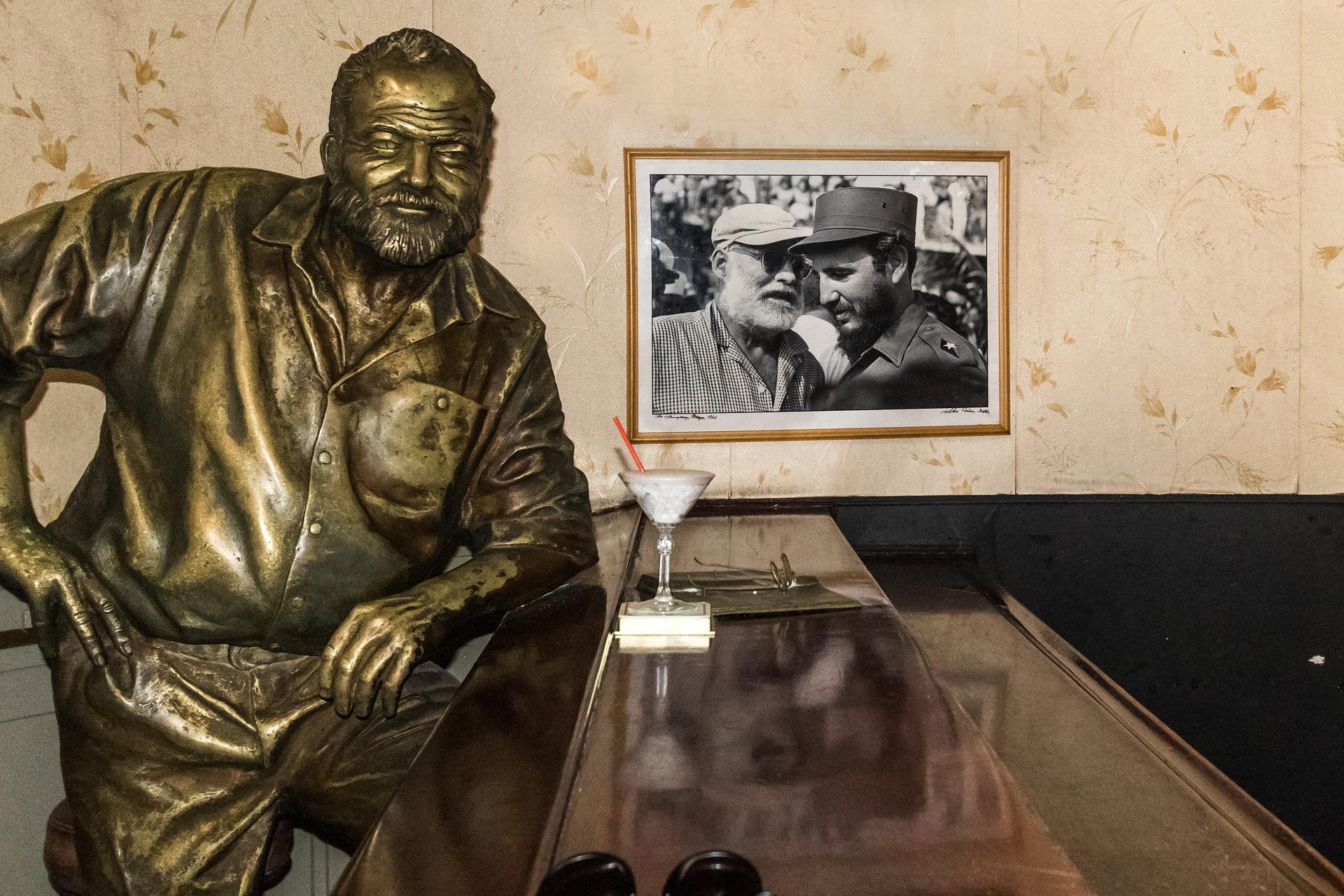 バーのカウンターに座るヘミングウェイの銅像